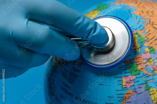 hand with blue glove auscultating the terrestrial globe Canvas Print