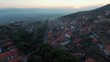 Aerial view of Birgi Odemis with a drone 4K. The old historical village, which was built on the skirts of the mountain, has pine trees and stone houses with a red tiled roof accompanied by sunset.