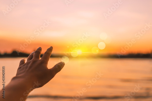 Foto Woman hands reach out to the sky like praying in front of sky.