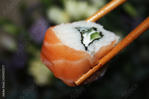 Salmon sushi nigiri in chopsticks over dark background macro shot Wallpaper Mural