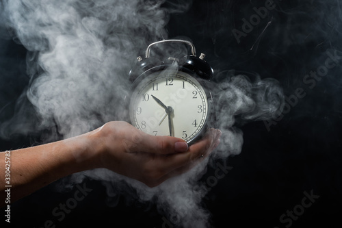 A woman holds an alarm clock in a studio full of smoke Canvas Print