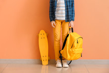 Cute Little Boy With Skate And Backpack Near Color Wall