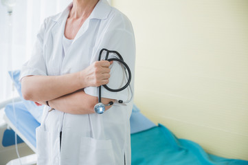 Doctor with stethoscope standing near patient bed. Medical healthcare and doctor service in hospital.