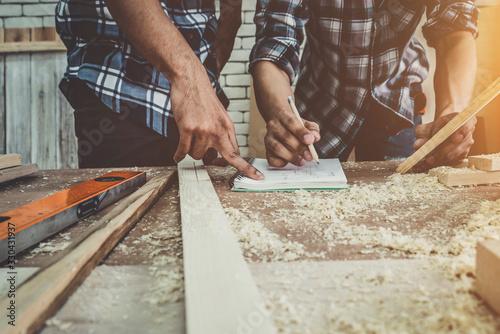 Obraz na plátne Carpenter working on wood craft at workshop to produce construction material or wooden furniture