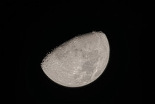 A Half Moon Floating In The Black Sky