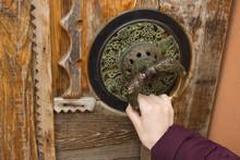 Knocker, Door Knocker, Fancy, Round Doorknob. A Hand Holds A Knocker, A Girl Wants To Open, To Knock A Massive Painted, Carved Wooden Door Of An Indian Oriental Vegan Goods Store.