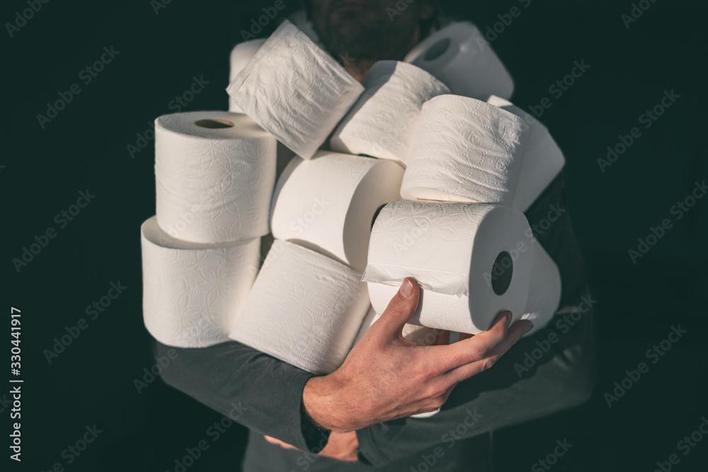Fototapeta Toilet paper shortage coronavirus panic buying man hoarding carrying many rolls at home in fear of corona virus outbreak closing shopping stores.