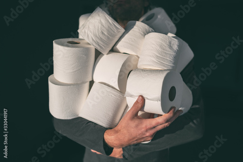 Toilet paper shortage coronavirus panic buying man hoarding carrying many rolls at home in fear of corona virus outbreak closing shopping stores. - 330441917