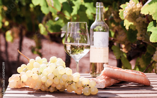 glass of White wine ripe grapes and bread on table in vineyard Wallpaper Mural