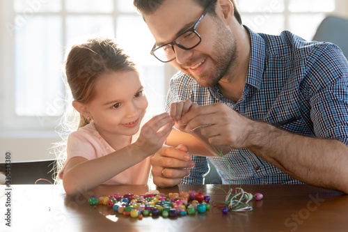 Fotografija Smiling young daddy helping small preschool daughter making bracelets with wooden bead pieces at home, head shot