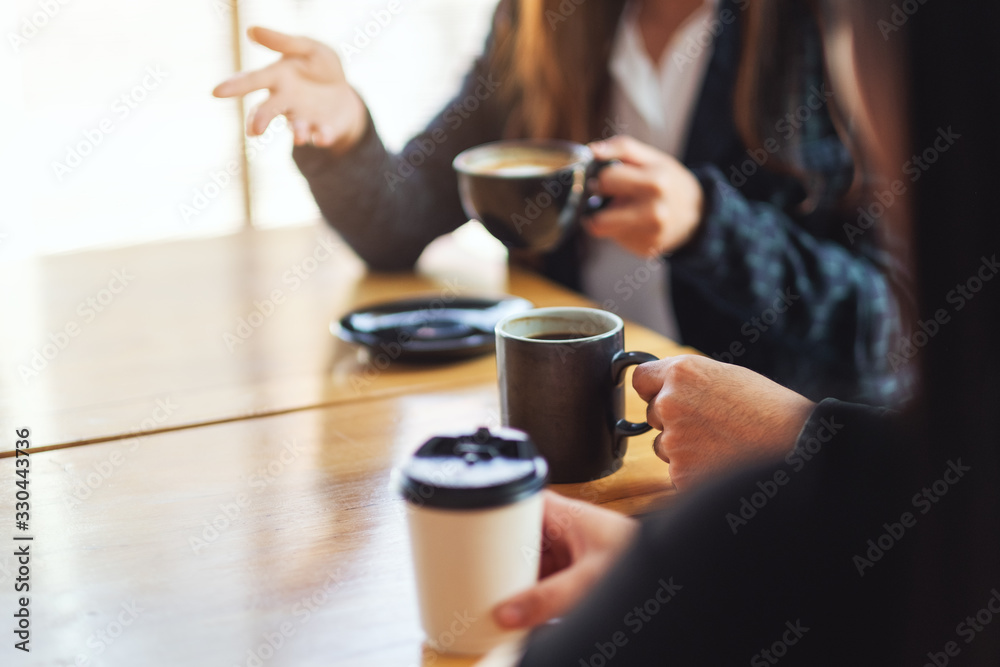 Fototapeta Closeup image of people enjoyed talking and drinking coffee together in cafe