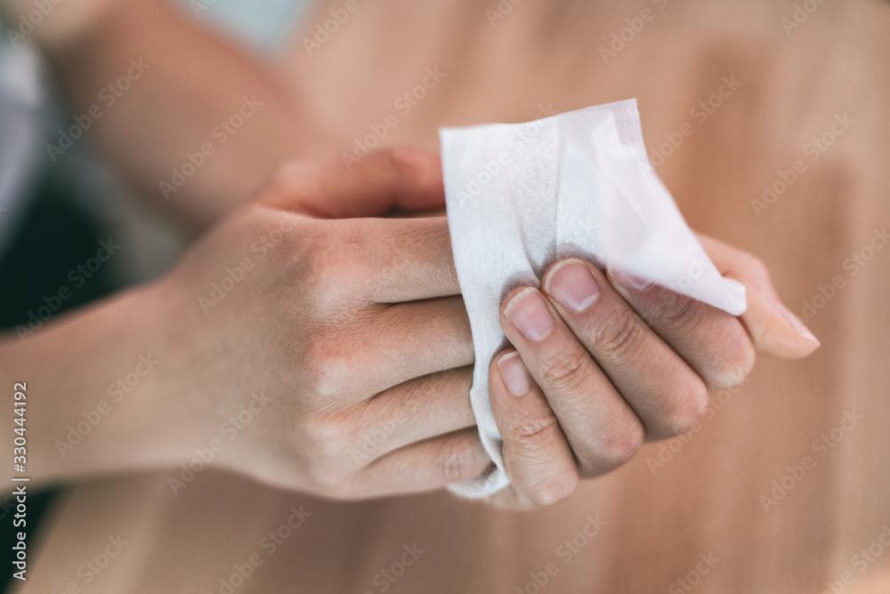 Fototapeta Corona virus hand hygiene coronavirus spreading protection woman cleaning hands washing with antibacterial disinfecting wipes at work.