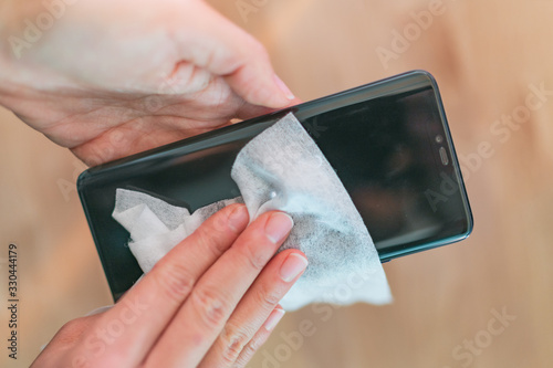Obraz Phone screen disinfecting wipe woman cleaning removing germs with antibacterial wet wipes for corona virus COVID-19 coronavirus prevention. - fototapety do salonu