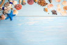 Beach Vacations Background. Frame Of Various Seashells And Starfish On Blue Paint Wooden Background. Space For Text, Top View