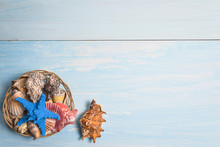 Beach Vacations Background. Basket With Various Seashells And Starfish On Blue Paint Wooden Background. Space For Text, Top View