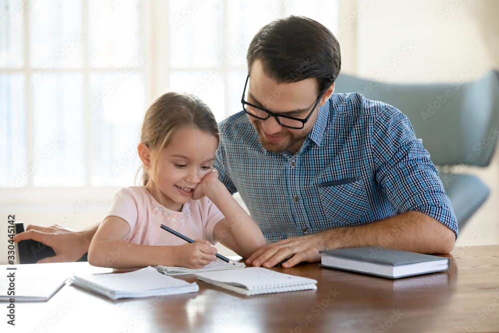 Fototapeta Young father in eyeglasses pleased to see little daughters' study success. Excited smiling small child girl enjoying learning with pleasant dad at home. Children education, home schooling concept.