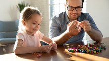 Happy Little Adorable Child Girl Sitting At Table With Pleasant Father, Stringing Colorful Wooden Beads On Threads. Smiling Dad And Small Cute Daughter Involved In Creative Activity, Making Bracelets.