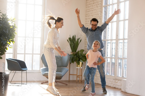 Overjoyed young married couple having fun, watching little preschool daughter dancing in living room. Happy small schoolgirl showing dance moves to excited cheerful supporting parents at home. - 330448386