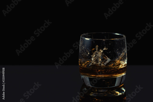 Whiskey splash in glass with ice on a dark background