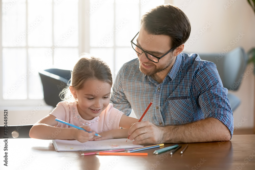 Fototapeta Head shot joyful young dad drawing pictures in paper album with happy small daughter, enjoying free leisure time at home. Smiling little kid girl learning painting with father, sitting at table.