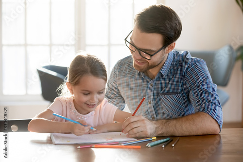 Fototapeta Head shot joyful young dad drawing pictures in paper album with happy small daughter, enjoying free leisure time at home. Smiling little kid girl learning painting with father, sitting at table. obraz