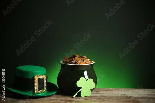 Obraz Pot with gold coins, hat and clover on wooden table against dark background, space for text. St. Patrick's Day - fototapety do salonu
