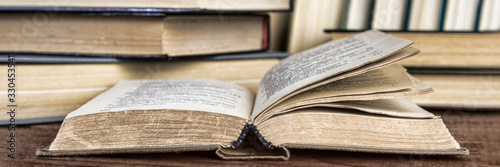 Photo An open hardback book on a table in a library