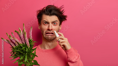 Indoor shot of frustrated man has watery red eyes, runny stuffy nose, uses drops, suffers from hay fever, has allergy on blooming plant, poses on pink background Canvas Print