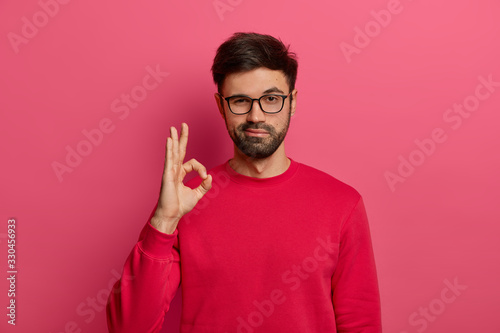 No problem concept. Bearded man makes okay gesture, has everything under control, all fine gesture, wears spectacles and jumper, poses against pink background, says I got this, guarantees something