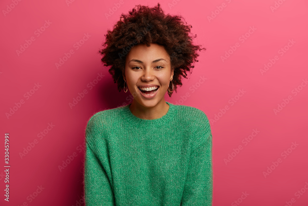 Fototapeta Portrait of good looking curly ethnic woman smiles broadly, enjoys day off, has happy talk with interlocutor, discusses holiday preparation, wears green sweater, isolated on pink background.