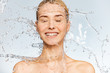 Leinwandbild Motiv Photo of  young  woman with clean skin and splash of water. Portrait of smiling woman with drops of water around her face. Spa treatment. Girl washing her body with water. Water and body.