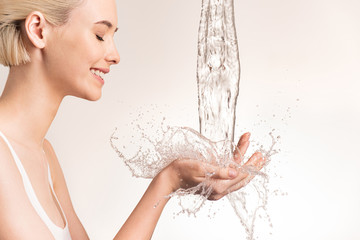 Photo of young woman with clean skin and splash of water. Smiling woman with drops of water near her face. Spa treatment. Girl washing hands with water. Water and body. Water falling on human hands