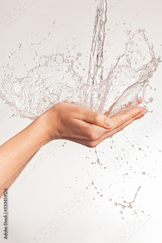 Obraz na plátně Photo of women's hands on which a stream of clean water pours