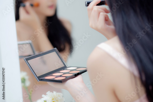 Photo Beauty young asian woman happy and smile with face looking mirror applying makeup with brusher of cheek in the room, beautiful of girl holding brush make-up on facial, skin care and cosmetic concept