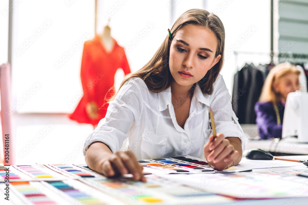 Fototapeta Portrait of young beautiful pretty woman fashion designer stylish sitting and working with color samples.Attractive young girl working with mannequins standing and colorful fabrics at fashion studio