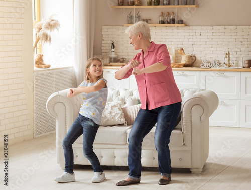 Obraz Cheerful older lady with her granddaughter dancing at home - fototapety do salonu