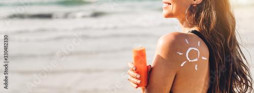Photo Woman wearing two piece bikini applying suncream with sun drawn on back and holding sunscreen lotion on the tropical beach