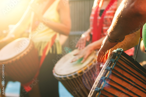 Close-up of people's hands playing on African djembe drums on a sunny summer evening Poster Mural XXL