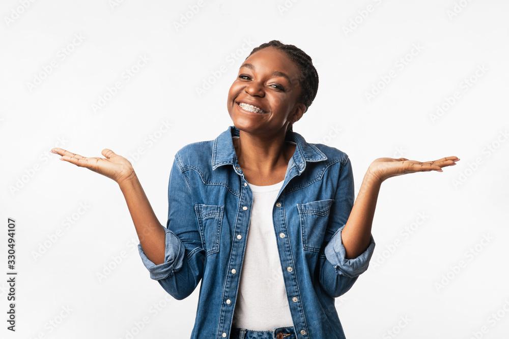 Fototapeta Positive African Girl Shrugging Shoulders Smiling To Camera, Studio Shot