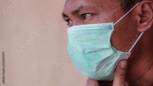 Photo Asian man wearing a medical face mask to anticipate the spread of diseases outbreak caused by viruses, such as coronavirus or covid-19 and avian influenza, which become a world pandemic
