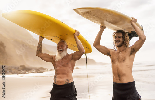 Happy friends surfing together on tropical ocean - Sporty people having fun duri Wallpaper Mural