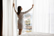 Attractive energetic happy young brunette woman wearing nightgown bathrobe, opening curtains on big panoramic window. Smiling lady enjoying starting of sunny day holiday vacation morning time.