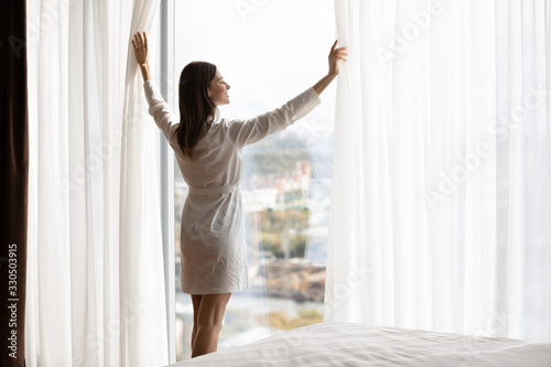 Obraz Attractive energetic happy young brunette woman wearing nightgown bathrobe, opening curtains on big panoramic window. Smiling lady enjoying starting of sunny day holiday vacation morning time. - fototapety do salonu