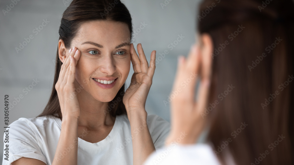Fototapeta Close up head shot happy female client satisfied with eyes area condition after beauty spa procedure, looking in mirror at bathroom. Smiling pretty brunette woman moisturizing face skin in morning.