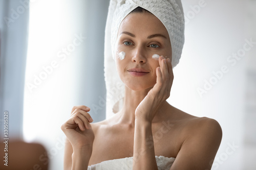 Fototapeta Head shot beautiful 30s lady looking in mirror, applying hydrating lotion creme on cheeks, finishing morning domestic skincare routine. Smiling woman grooming herself after showering in bathroom. obraz na płótnie