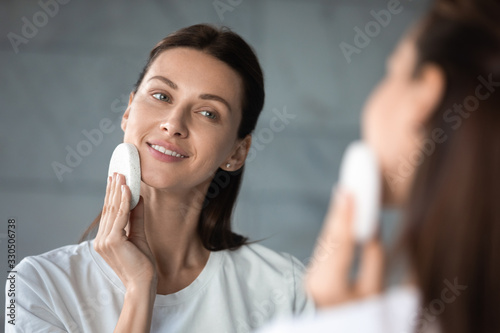 Pleasant attractive brunette woman looking at mirror, removing makeup in evening at bathroom Fototapete