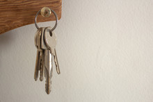 Bunch Of Keys Hanging On A Holder On A White Wall