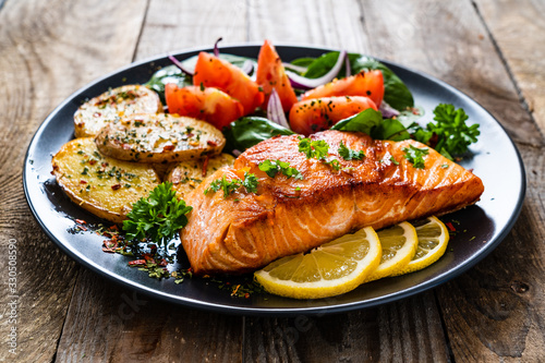 Fotografia Fried salmon steak with potatoes and vegetables on wooden table