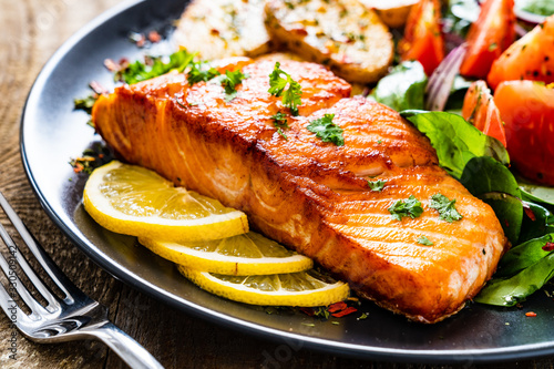 Fried salmon steak with potatoes and vegetables on wooden table Fototapeta