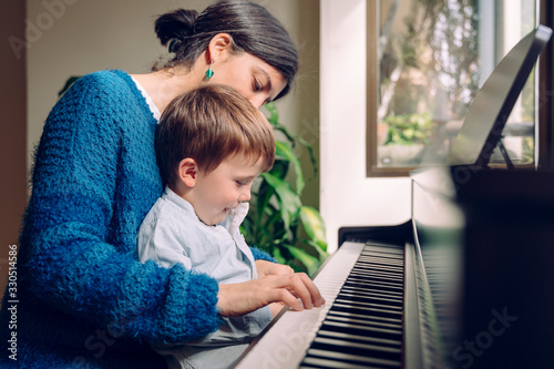 Fototapeta Family lifestyle spending time together indoors. Children with musical virtue and artistic curiosity. Educational musical activities for little kid. Mom teaching her son at home piano lessons. obraz